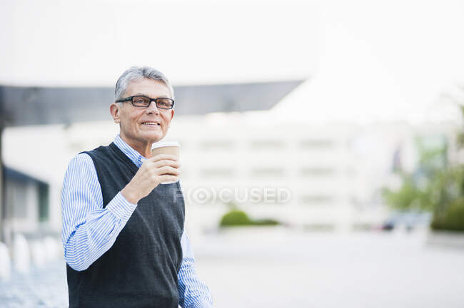 Portrait of senior businessman with coffee to go outdoors — Stock Photo