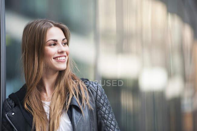 Jeune femme réfléchie souriant tout en regardant loin pendant la journée ensoleillée — Photo de stock