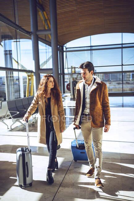 Coppia d'affari che parla mentre cammina con i bagagli nell'area di partenza dell'aeroporto — Foto stock