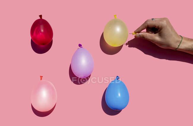 Студийный снимок руки человека, пытающегося проткнуть красочные водяные шары кнопкой — стоковое фото