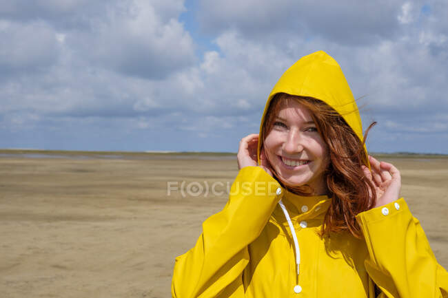 Ritratto ravvicinato di ragazza adolescente rossa spensierata che indossa un impermeabile giallo mentre si trova in spiaggia contro il cielo nella giornata di sole — Foto stock