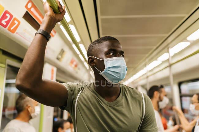 Jovem usando máscara olhando para longe enquanto estava de pé no trem do metrô — Fotografia de Stock