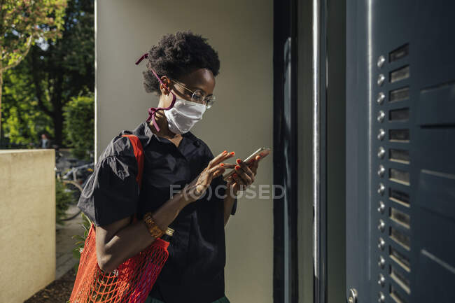 Jovem mulher vestindo máscara protetora têxtil em pé na frente da porta de entrada usando smartphone — Fotografia de Stock
