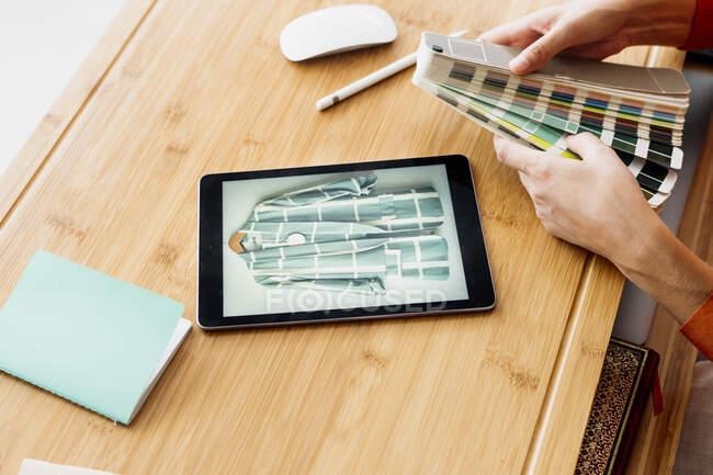 Primer plano del diseñador de moda que trabaja en el escritorio con la tableta y la muestra de color - foto de stock