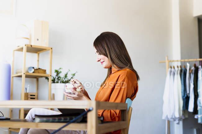 Designer de moda feminina almoçando no escritório em casa — Fotografia de Stock