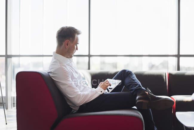 Бізнесмен сидить на дивані, користуючись цифровим планшетом. — стокове фото