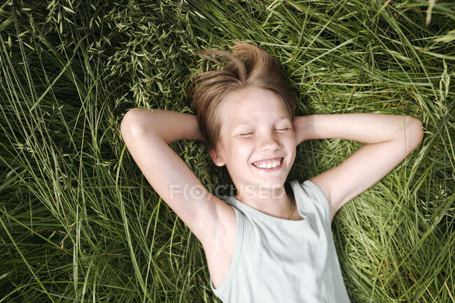 Portrait of happy boy with eyes closed lying on a meadow in summer — Stock Photo