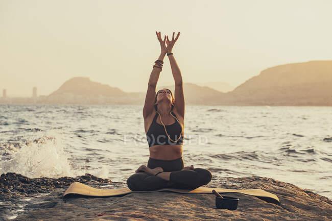 Зрелая женщина практикует йогу на скалистом пляже вечером — стоковое фото