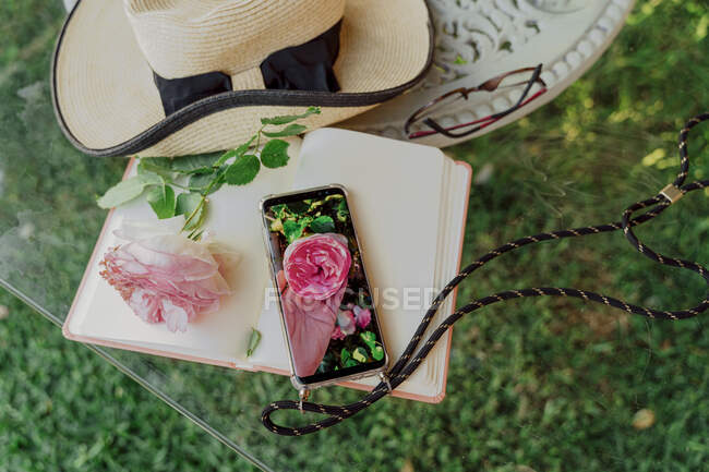 Summer hat, book, rose blossom and smartphone with photo of rose blossom lying on glass pane — Stock Photo