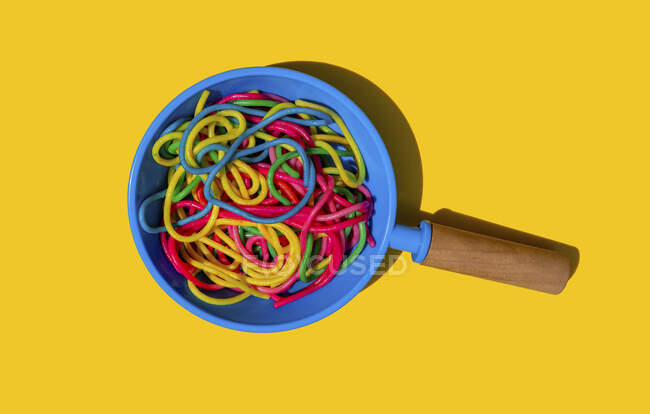 Studio shot of toy frying pan with colorful pasta — Stock Photo