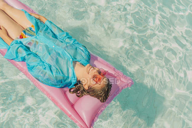 Mujer con abrigo de lluvia azul relajante en cama de aire rosa en la piscina - foto de stock