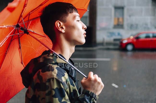 Людина з парасолькою на вулиці під час дощового сезону — стокове фото
