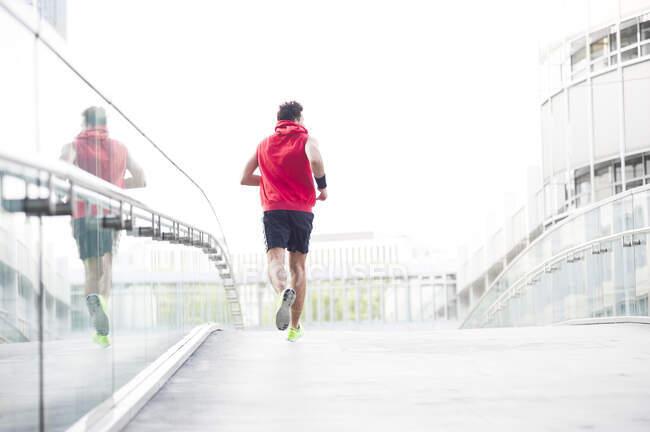 Vista trasera del joven trotando en la pasarela de la ciudad - foto de stock