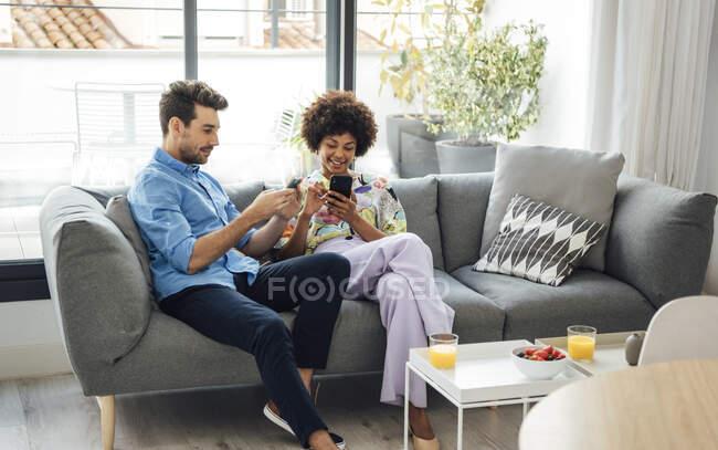 Multi-ethnic couple using smart phones while sitting on sofa in penthouse — Stock Photo