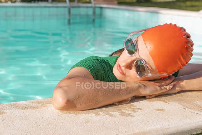 Retrato de mujer con gorra de natación roja y gafas de sol apoyadas en la piscina - foto de stock