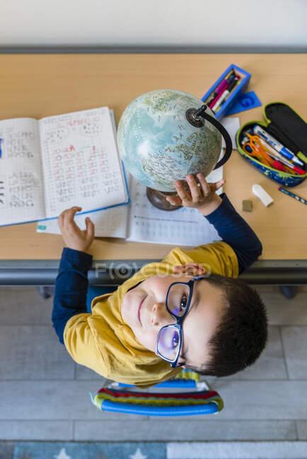 Милий хлопчик вивчає глобус, сидячи за столом під час карантину. — стокове фото