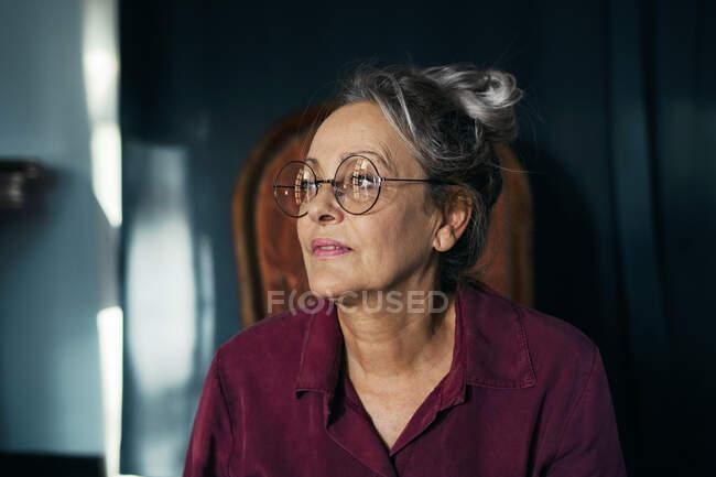 Gros plan d'une femme âgée réfléchie portant des lunettes et regardant ailleurs, assise à la maison — Photo de stock
