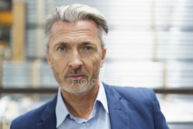 Ritratto di un uomo d'affari maturo e sicuro di sé in una fabbrica — Foto stock