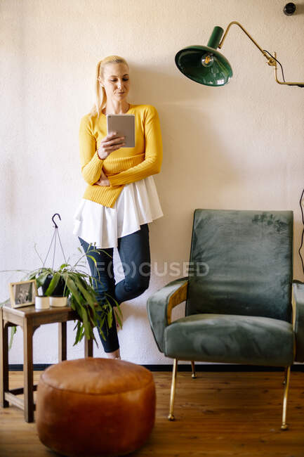 Жінка-блондинка, що стоїть вдома, користуючись цифровою табличкою. — стокове фото