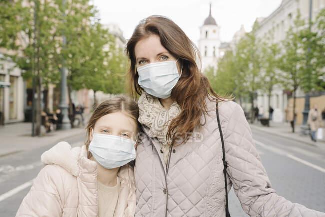 Мати з донькою в масках стоять на вулиці в місті. — стокове фото