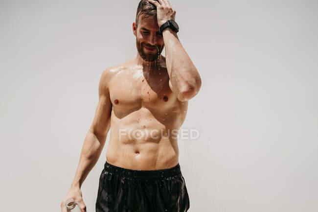 Atleta masculino desnudo refrescante con agua - foto de stock