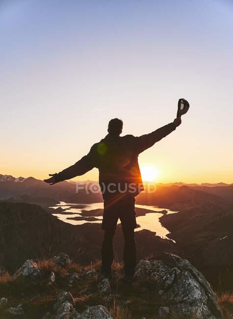 Turista masculino de pie con los brazos extendidos en la montaña durante el atardecer, León, España - foto de stock