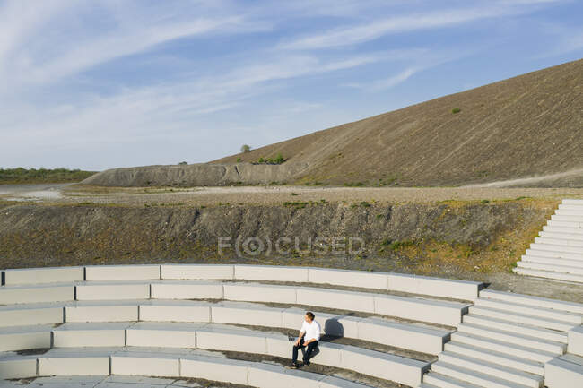 Hombre profesional sentado en el anfiteatro pasos contra el cielo en el día soleado - foto de stock