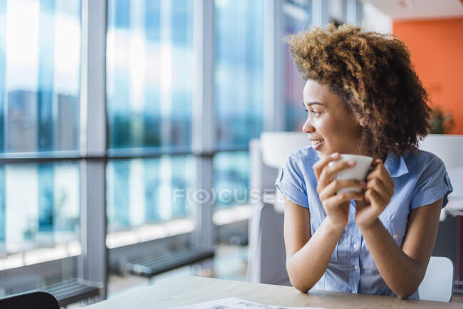Young woman sitting in modern office, drinking coffee — Stock Photo