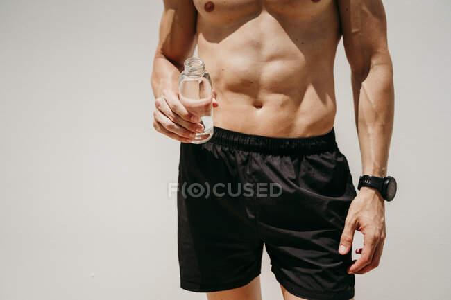 Atleta masculino desnudo sosteniendo una botella de agua - foto de stock
