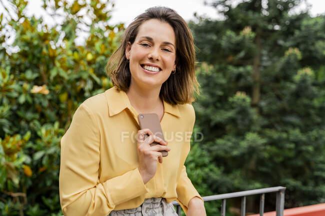 Портрет усміхненої жінки зі смартфоном на балконі. — стокове фото