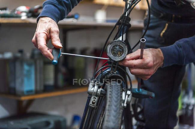 Mecânico de bicicletas trabalhando na loja de bicicletas — Fotografia de Stock