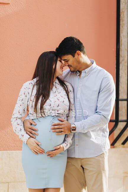 Романтическая будущая пара, стоящая с руками на животе у розовой стены в городе — стоковое фото