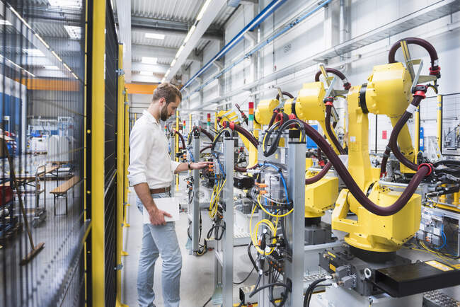 Side view of confident male machinery expert examining robotic arm in factory — Stock Photo