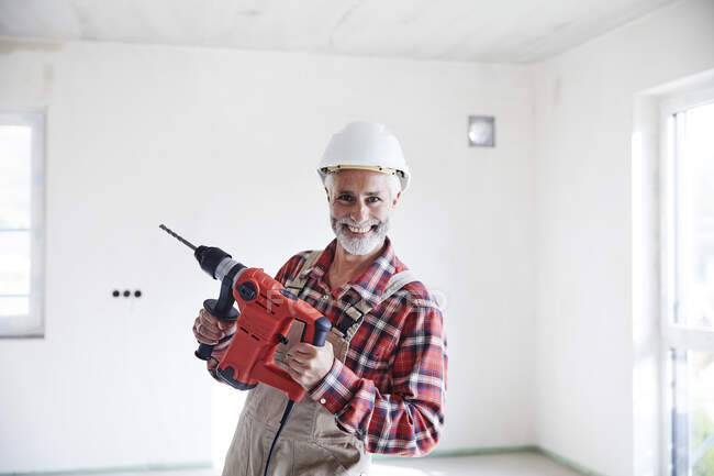 Construction worker with drill at construction site — Stock Photo
