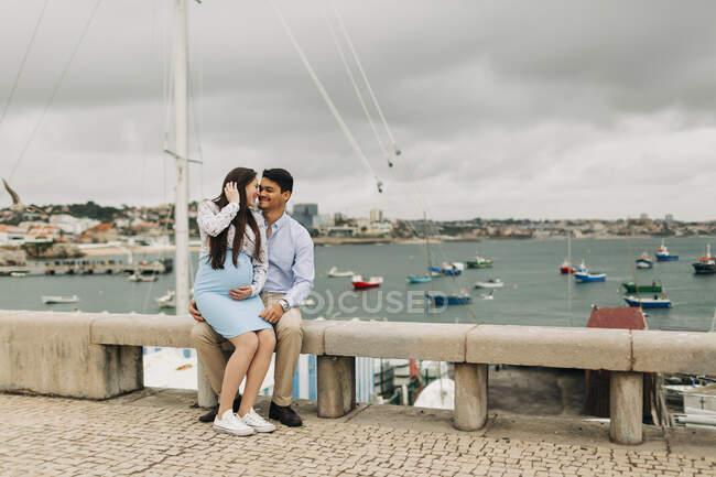 Романтическая будущая пара, сидящая на стене в порту, Кашкайш, Португалия — стоковое фото