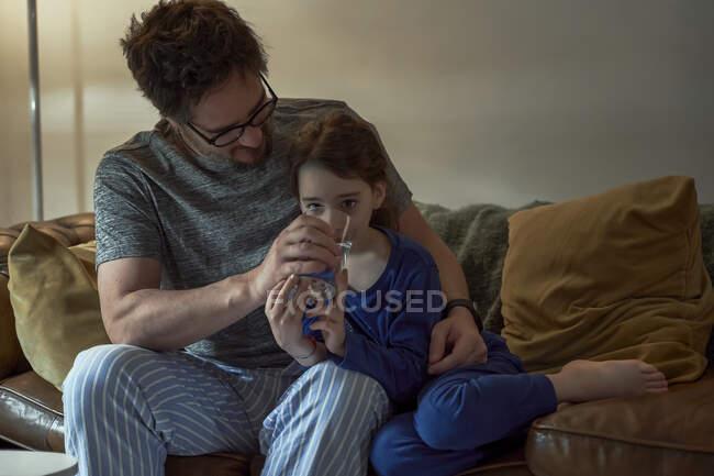 Padre ayudando a la hija enferma en el agua potable mientras está sentado en el sofá en la sala de estar en casa - foto de stock
