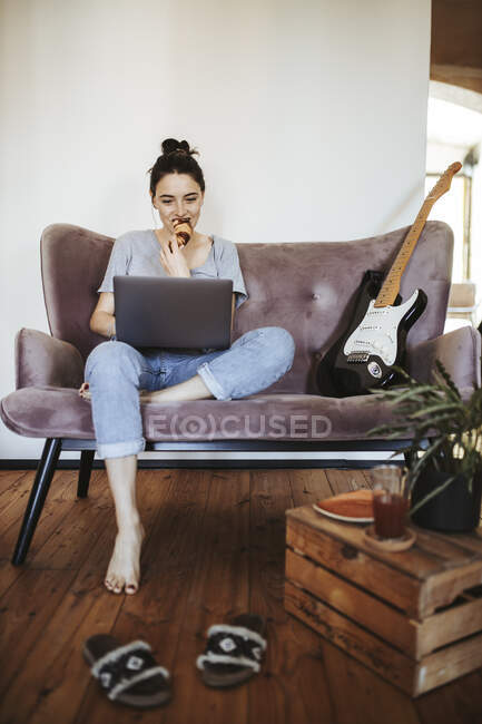 Young woman sitting on couch at home eating croissant while looking at laptop — Stock Photo