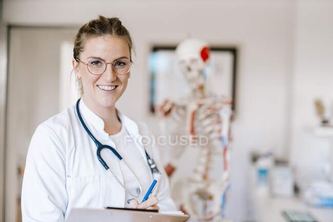 Retrato de doctora sonriente con esqueleto anatómico en el fondo - foto de stock