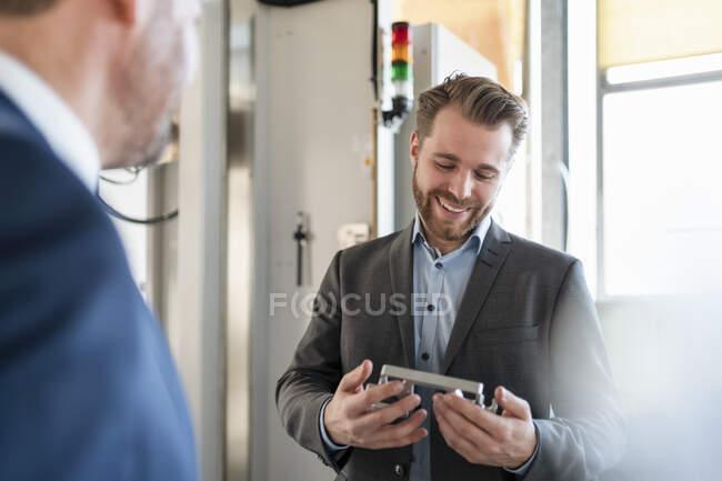 Un jeune homme d'affaires souriant dans une usine tenant une pièce — Photo de stock