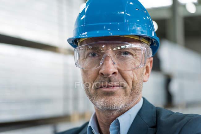 Портрет зрілого бізнесмена, одягненого в твердий капелюх і захисні окуляри на заводі. — стокове фото