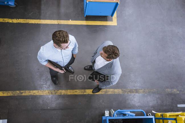 Краєвид двох бізнесменів, які розмовляють на фабриці. — стокове фото