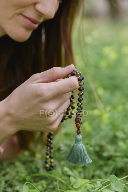 Близько середнього віку жінка тримає намистинки, медитуючи над травою землі. — стокове фото