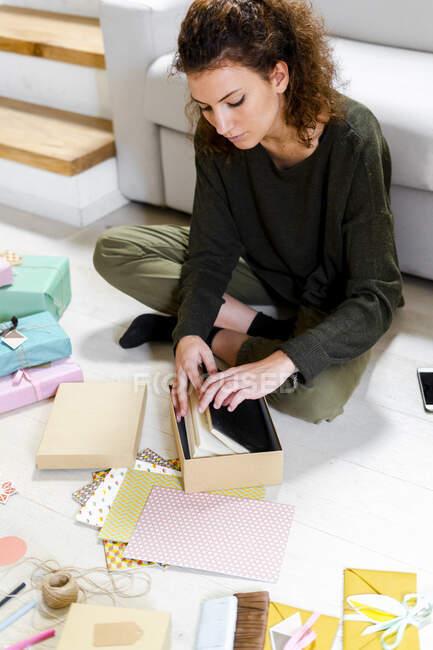 Молодая женщина, сидящая на полу дома, упаковывая подарок — стоковое фото