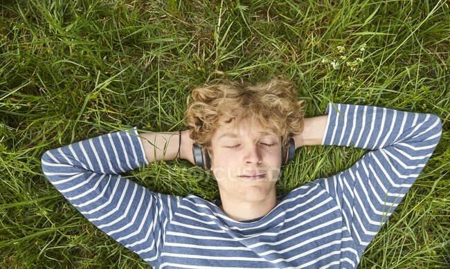 Портрет молодого человека с вьющимися светлыми волосами, лежащего на лугу и слушающего музыку в наушниках — стоковое фото