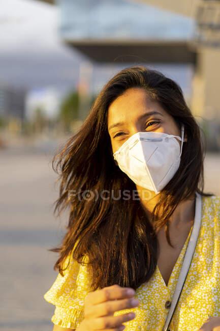 Mujer joven y feliz con mascarilla en la ciudad - foto de stock