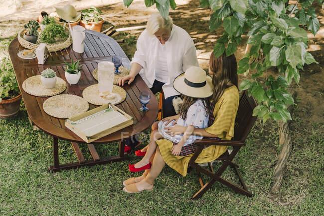 Multi-generation family enjoying picnic at table in yard — Stock Photo