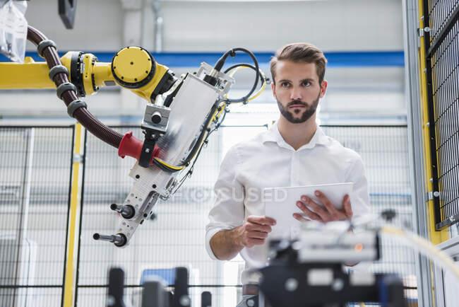 Молодий робототехнік відводить погляд убік, стоячи на заводі. — стокове фото