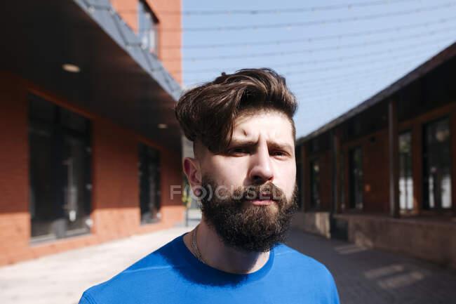 Портрет молодого человека, идущего по городу, выглядящего серьезным — стоковое фото