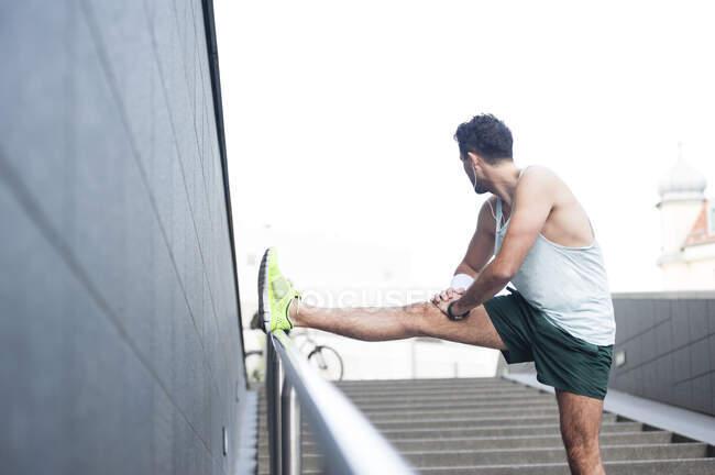 Молодий чоловік розтягує ногу на поручні в місті. — стокове фото