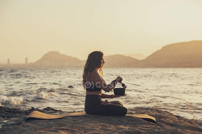 Зрелая женщина медитирует с пением чаши практикуя йогу на скалистом пляже вечером — стоковое фото